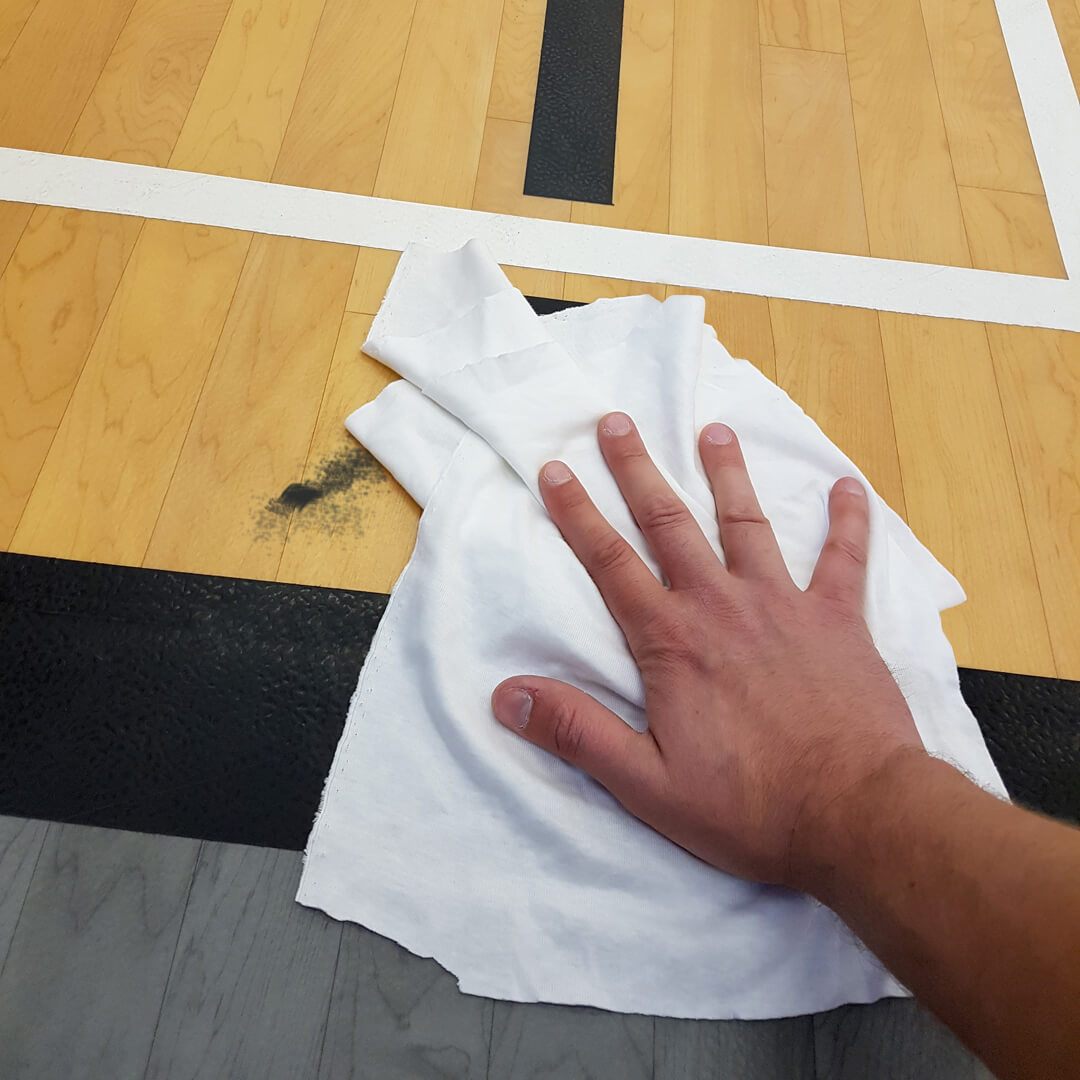 Spot cleaning gymnasium floor with white rag